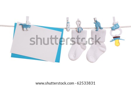 Baby goods and blank note hanging on the clothesline - stock photo