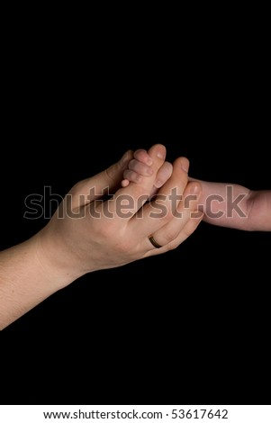 Baby hand and Father hand on black background - stock photo