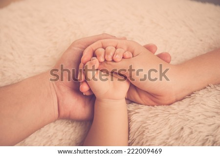 Baby hand. Closeup of baby hand into parents hands. Family concept. Baby holding mother's finger - stock photo