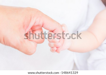 baby hand holding adult finger - stock photo