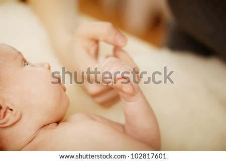 Baby hand holding mother finger - stock photo