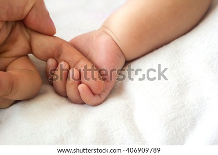 Baby hand holding mother finger. Trust relationship. Abstract background. With space area.