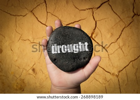 """Baby Hand Holding Pebble With the Word """"Drought"""" - stock photo"""