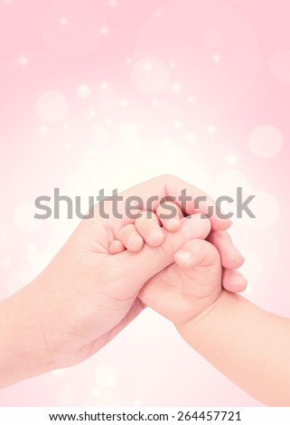 baby hand in hand of love with pink glitter background - stock photo