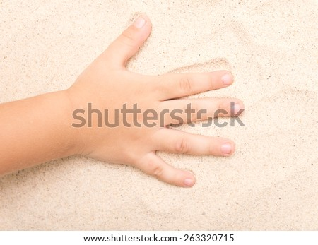 baby hand on a sand - stock photo