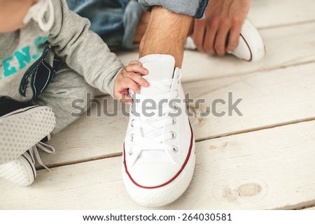 Baby hand on white shoe of the father close-up - stock photo