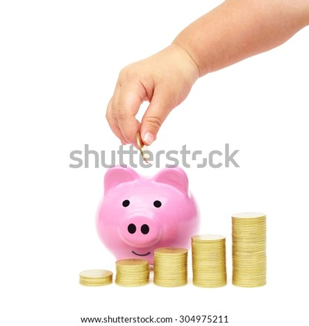baby hand putting a golden coins into a pink piggy bank with piles of golden coins arranged as a graph - saving money for security in life concept - stock photo