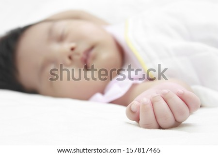 baby hand, sleeping on white bed - stock photo