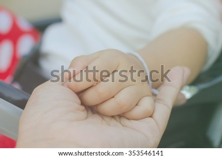 baby hand with mother hand in vintage tone style - stock photo
