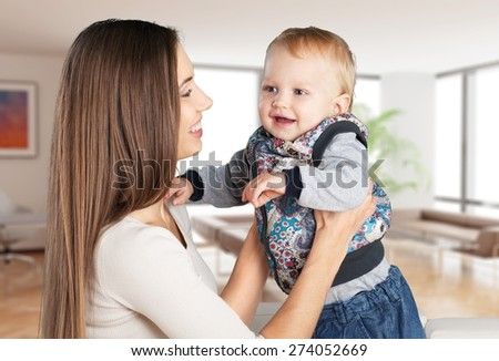Baby. Happy family. Mother throws up  baby, playing at home - stock photo