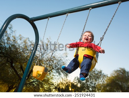 Baby Having Fun on Playground Swing - stock photo