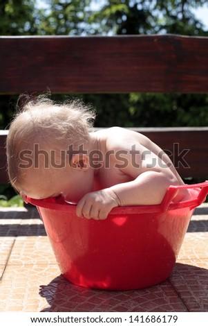 Baby having fun swimming in a bowl - stock photo