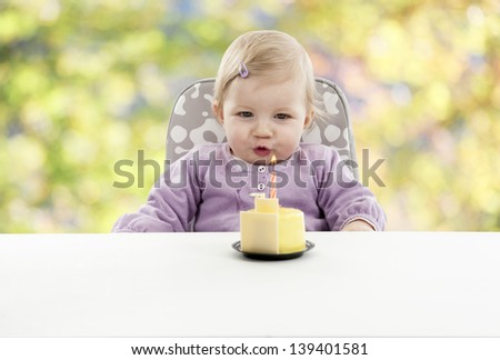 baby having her first birthday, green and yellow blurred background - stock photo