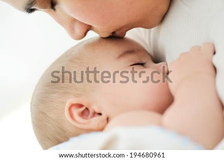 Baby having mom's care - stock photo