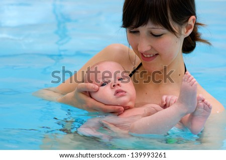 baby having swimming lesson with mother - stock photo