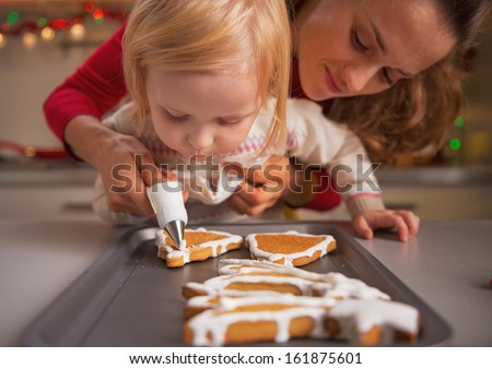 Baby helping mother decorate homemade christmas cookies with glaze - stock photo