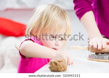 Baby helps mother with  baking gingerbread cookies in kitchen