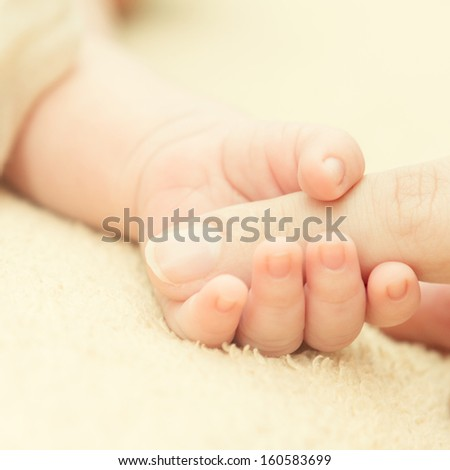 Baby hold mother's finger. - stock photo