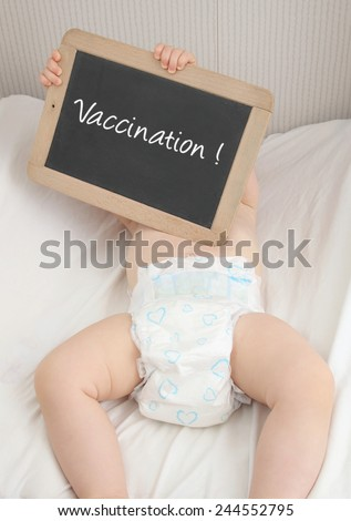 Baby holding a blackboard with writing VACCINATION - stock photo