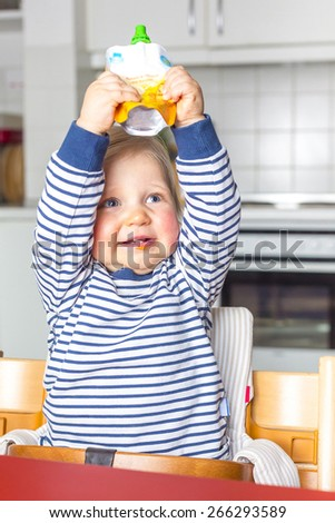 Baby holding a pack of fruit puree - stock photo