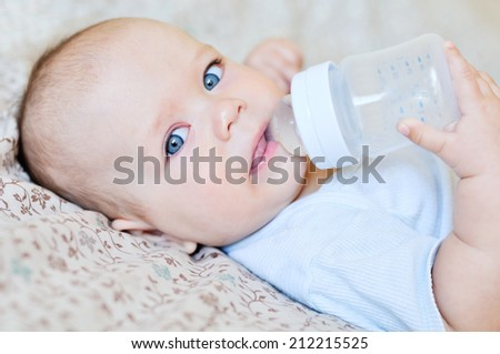 baby holding bottle and drinking water - stock photo
