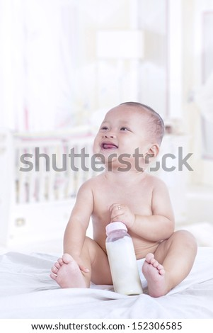Baby holding bottle of milk at home , vertical shot - stock photo