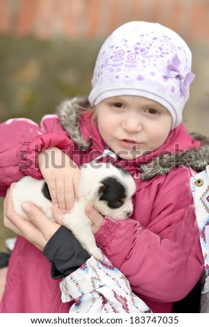 Baby holding cute puppy Jack Russel in hands