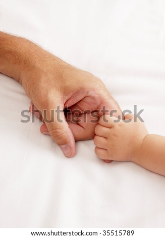 Baby holding dads hand