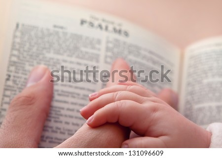 Baby holding father'??s finger as he points to Psalms verse - stock photo