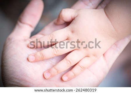 baby holding father's hand, image with shallow depth of field