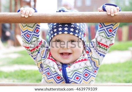 baby holding of climber on playground