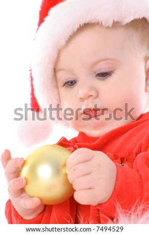 baby holding ornament with santa hat upclose - stock photo