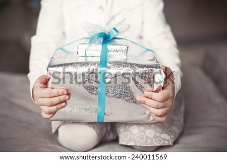 Baby holds a Christmas present box in hands - stock photo