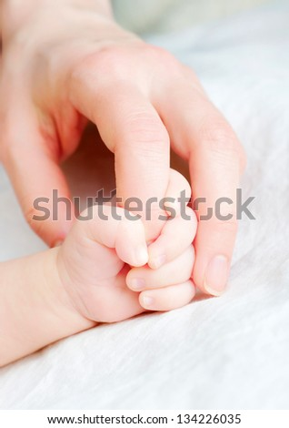 Baby holds mother's finger - stock photo