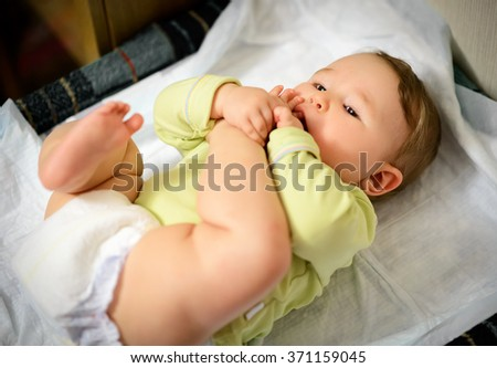 Baby hugged his leg and sucking toe - stock photo