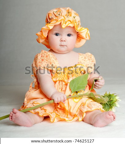 baby in a beautiful dress with a sunflower - stock photo