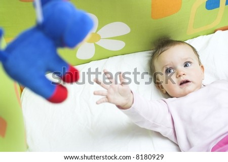 Baby in a crib - reaching for a toy - stock photo