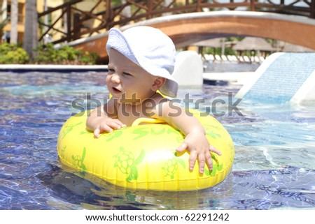 Baby in a floating in a tropical resort pool - stock photo