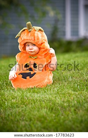 Baby in a Halloween pumpkin costume sitting on grass