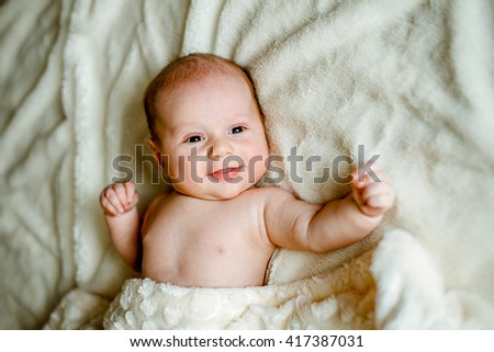 baby in a knitted cap is covered with a blanket and smiling - stock photo