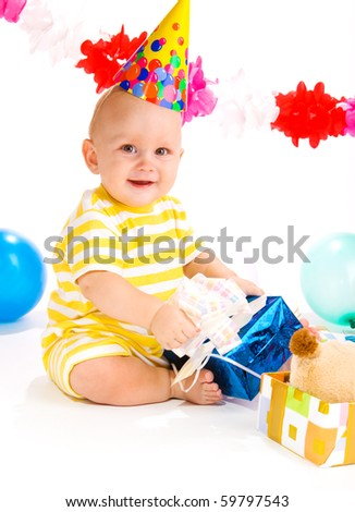 Baby in a party hat happy to receive a present - stock photo