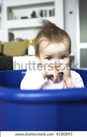Baby in a plastic tray - sad face expression - stock photo