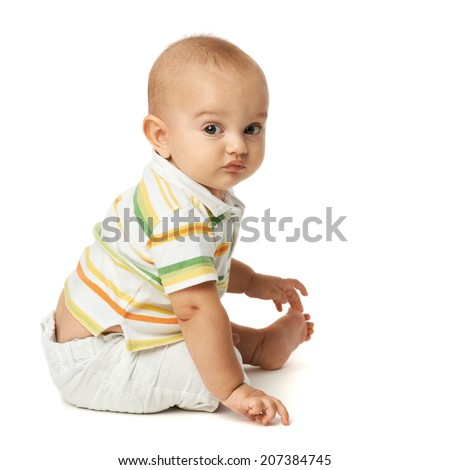 baby in a striped sweater sits on white background