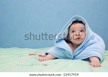 Baby in a towel creeps on a bed and looks upwards