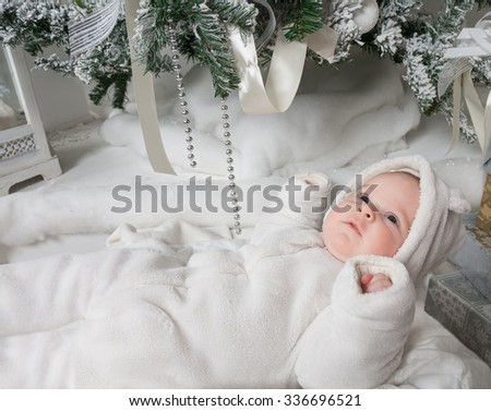 Baby in a white fur suit lies near the Christmas tree next to the gifts - stock photo