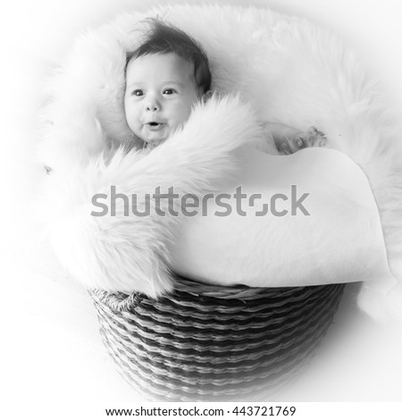 Baby in basket,A beautiful caucasian white baby girl portrait with cute facial expression lying in a basket - stock photo