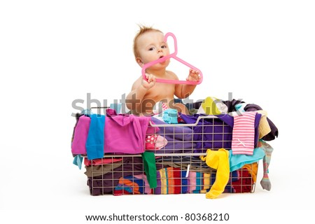 Baby in basket with clothes with hanger, isolated on white - stock photo
