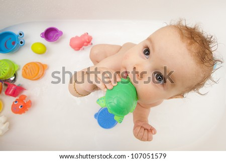 Baby in bath tub with toys - stock photo