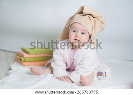 baby in bathrobe with towels sitting in the bathroom and playing - stock photo