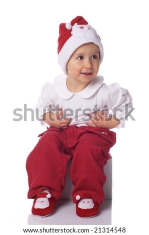 baby in big Santa Claus hat sitting on a box,  on white background background
